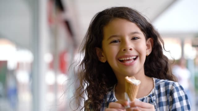 beautiful little girl enjoying a delicious ice cream at the mall - gelato video stock e b–roll