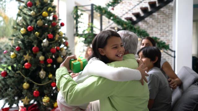vídeos y material grabado en eventos de stock de hermosa niña entregando abuelo un regalo de navidad abrazando muy cariñosamente mientras la familia se sienta en el fondo - christmas family