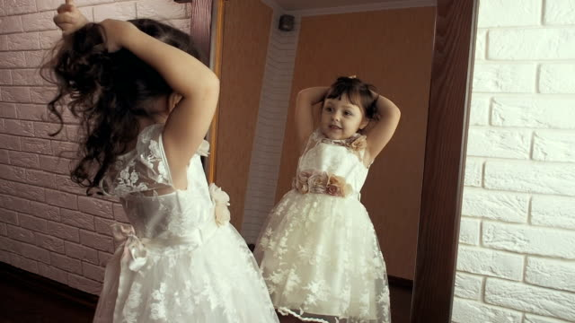 Beautiful little girl is looking in the mirror. Beautiful little girl is looking in the mirror. princess stock videos & royalty-free footage