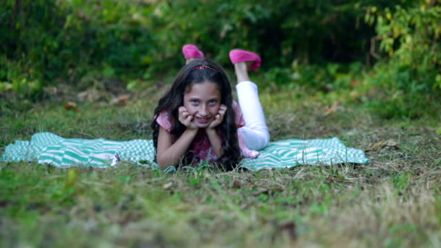 Beautiful little girl lying on the grass and smiling. video