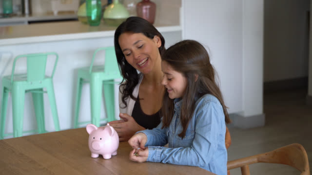 Beautiful little girl saving money in her piggy bank and mom sitting next to her talking and smiling Beautiful little girl saving money in her piggy bank and mom sitting next to her talking and smiling very happy piggy bank stock videos & royalty-free footage