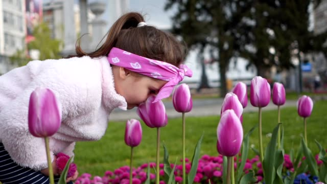 Beautiful little girl smelling pink tulips in the city centre