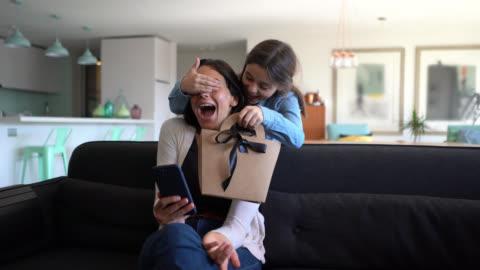 vidéos et rushes de belle petite fille surprenant sa maman tandis qu'elle est assise sur le divan utilisant son smartphone avec un cadeau pour la journée de mère - cadeau