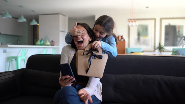 Beautiful little girl surprising her mom while she is sitting on couch using her smartphone with a gift for mother's day Beautiful little girl surprising her mom while she is sitting on couch using her smartphone with a gift for mother's day - Celebration concepts mothers day stock videos & royalty-free footage