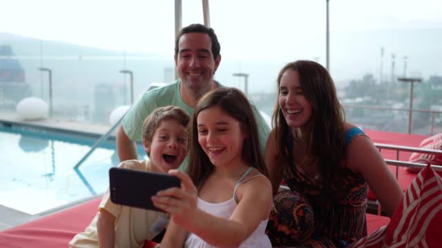 bella bambina che si fa un selfie con i suoi genitori e il fratello godendosi una giornata nella piscina sul tetto tutti sorridenti - america latina video stock e b–roll