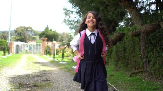 vidéos et rushes de belle petite fille marchant de retour à la maison après l'école souriant très heureux - uniforme