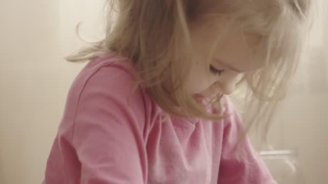 vacker liten flicka tittar på videor av sig själv på en smartphone - endast flickor bildbanksvideor och videomaterial från bakom kulisserna