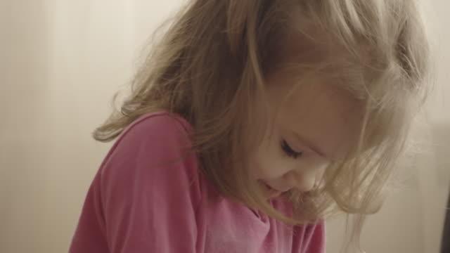 güzel küçük kız bir akıllı telefon üzerinde kendini videoları izlerken - dijital yerli stok videoları ve detay görüntü çekimi