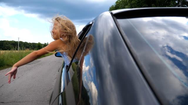 bella bambina con lunghi capelli biondi che mettono la mano fuori dalla finestra aperta che muove auto per sentire la brezza. felice ragazzino appoggiato fuori dal finestrino dell'auto e agitando il braccio nel vento mentre attraversa la strada di campagna - braccio umano video stock e b–roll