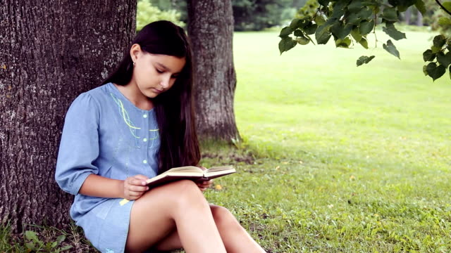 A beautiful little girl with long hair reads a book sitting under a tree and dreams about something pleasant video