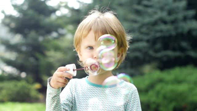 bella bambina con bolle di sapone. rallentatore. primo piano - abbigliamento da neonato video stock e b–roll