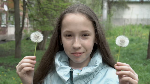 Beautiful little teen girl smiling and playing with white fluffy dandelions in the backyard of the house. She looks at the camera and covers her eyes with dandelions. Portrait. Close up. Concept. 4K.