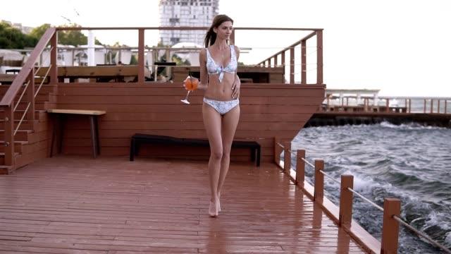 水着で光で美しい足の長い女の子歩く桟橋にカクテル グラスと裸足手に。海辺。フロント ビュー - スタイリッシュ点の映像素材/bロール