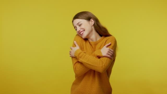 vidéos et rushes de belle belle fille heureuse avec le cheveu brun dans le pull embrassant elle-même et souriant - admiration