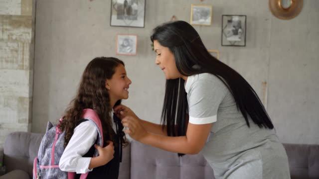 vídeos y material grabado en eventos de stock de hermosa madre amorosa besando a su hija en la frente antes de salir a la escuela en casa - preparación