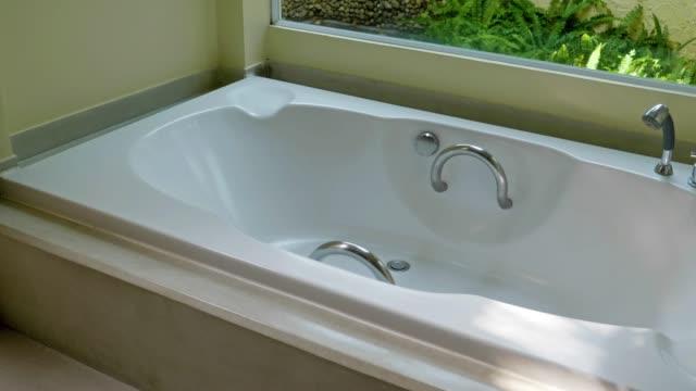 schöne luxus badezimmer interieur mit waschbecken wasserhahn und badewanne - wohngebäude innenansicht stock-videos und b-roll-filmmaterial