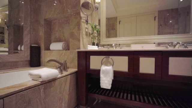 wunderschönes luxuriöses badezimmer mit waschbecken und badewanne - wohngebäude innenansicht stock-videos und b-roll-filmmaterial
