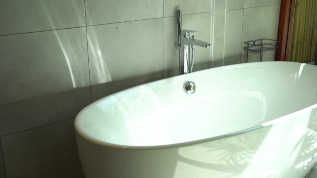 schöne luxus-badezimmer-interieur mit waschbecken wasserhahn und badewanne - wohngebäude innenansicht stock-videos und b-roll-filmmaterial