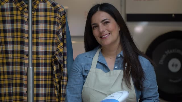 Beautiful mature business owner of a laundry service holding a garment steamer while facing camera smiling