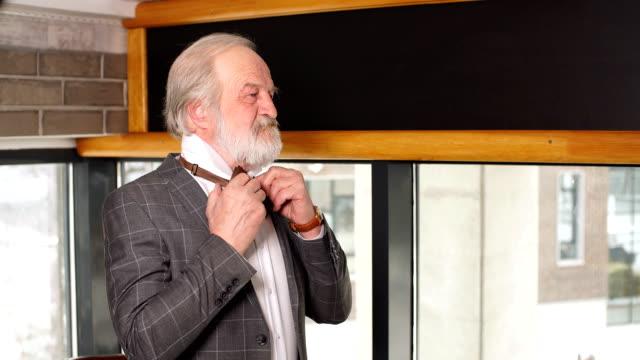beautiful mature businessman in a classic costume dresses up for a date - solo un uomo maturo video stock e b–roll