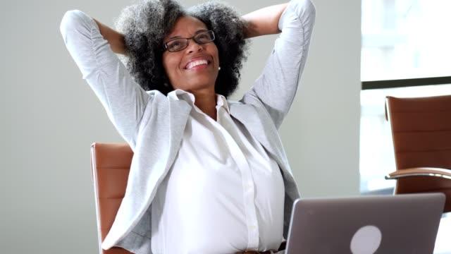 stockvideo's en b-roll-footage met mooie rijpe zakenvrouw is opgelucht te hebben voldaan aan een deadline - happy woman