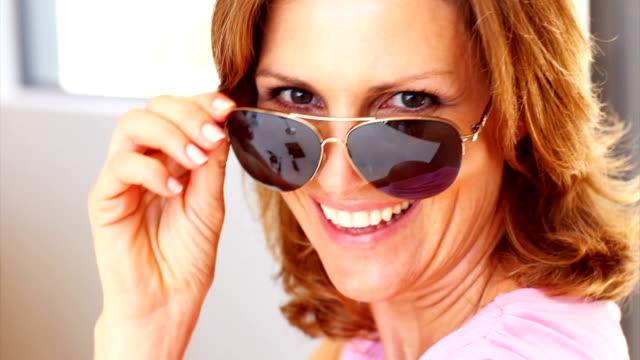 bella donna matura indossare gli occhiali da sole - femminilità video stock e b–roll