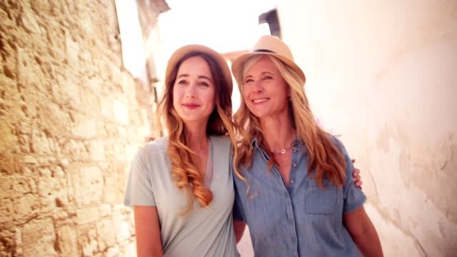 Beautiful mature mother and daughter walking in old stonebuilt streets video