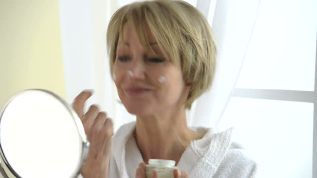 Beautiful Mature Woman Applying Moisturizer; HD Photo JPEG, dolly. video