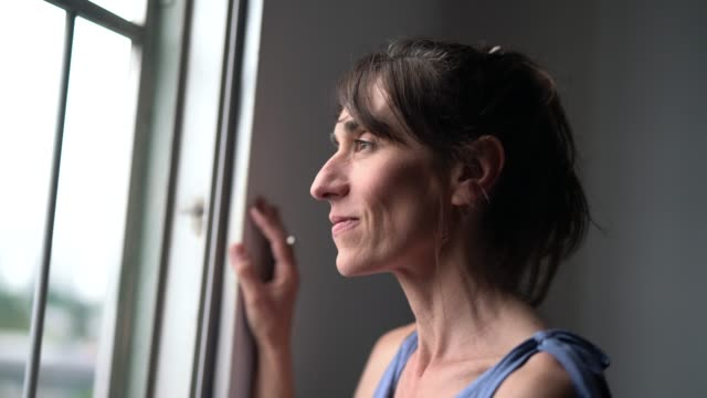 Beautiful Mature Woman Looking Out Of Window Portrait hope concept stock videos & royalty-free footage