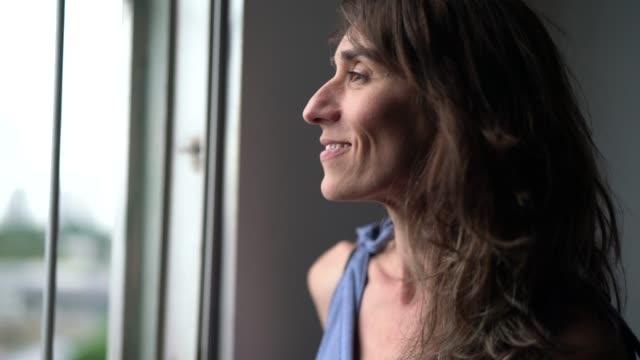 vacker mogen kvinna som tittar ut ur fönster - titta på utsikt bildbanksvideor och videomaterial från bakom kulisserna