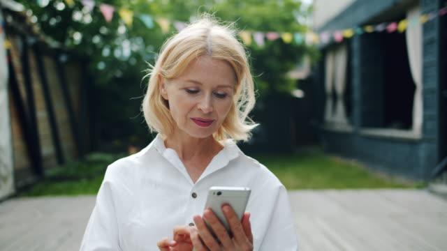 vídeos y material grabado en eventos de stock de hermosa mujer madura usando teléfono inteligente tocando la pantalla al aire libre - pelo rubio