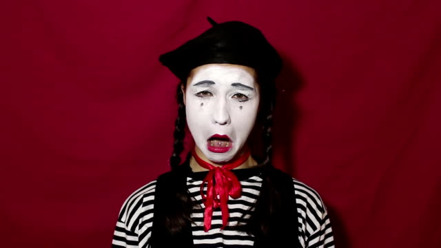 beautiful mime girl depicts a strong upset and crying, looking at the camera. a beautiful mime girl in a striped shirt shows a sad face and tears. - гримировальные краски стоковые видео и кадры b-roll