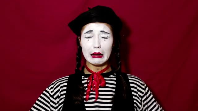 美しいマイムガールは、カメラを見て、強い動揺と泣き声を描いています。ストライプのシャツを着た美しいマイムガールは、悲しい顔と涙を見せます。 - グリースペイント点の映像素材/bロール