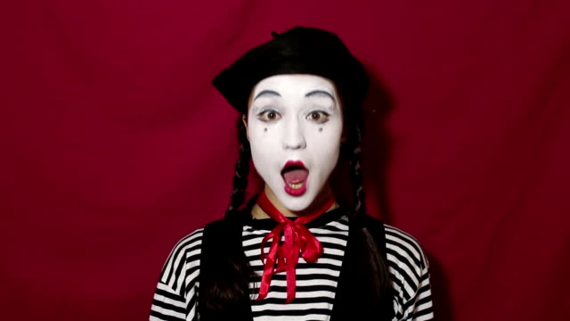 beautiful mime girl nods her head affirmatively and says yes while looking at the camera. beautiful mime girl in a striped shirt nods her head affirmatively and smiles. - гримировальные краски стоковые видео и кадры b-roll