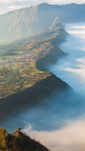 vídeos de stock e filmes b-roll de beautiful misty landscape  movement around hillside village of bromo, indonesia 4k time lapse (vertical screen, pan shot) - vertical