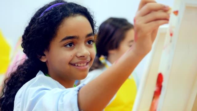 Beautiful Mixed Race Preteen Painting in Art Class