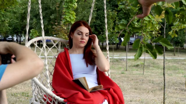A beautiful model girl poses for two photographers at a fashion shoot. A man and a woman take pictures of her outdoors, on a swing in a city park at sunset. Fashion portrait. Close-up. 4K.