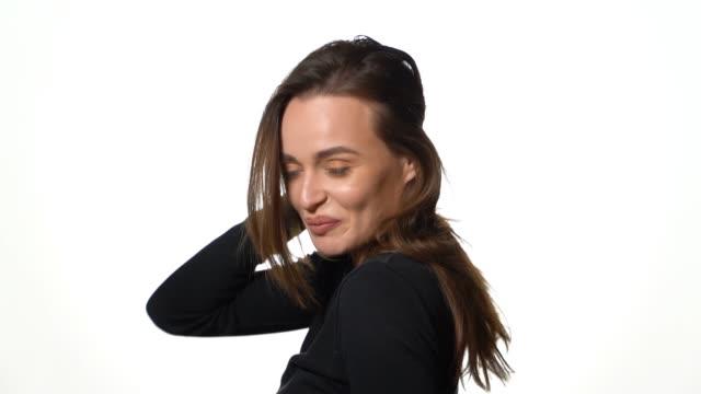 stockvideo's en b-roll-footage met een mooi model in een zwarte trui kantelt haar haar terug en glimlacht op een witte achtergrond in de studio. - curly brown hair