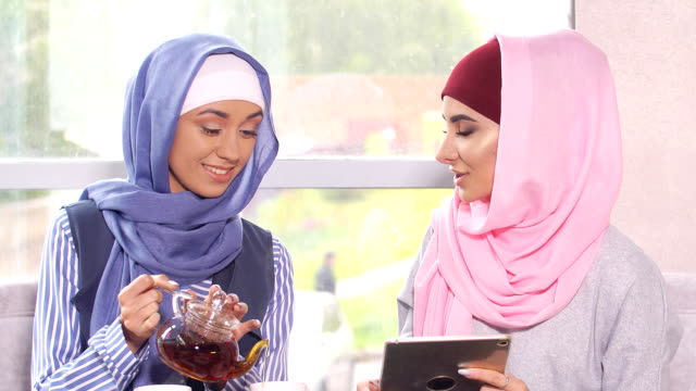 beautiful modern muslim women communicate and drink tea in coffee shop - abbigliamento modesto video stock e b–roll