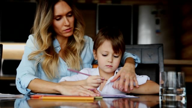 Beautiful mom helps her son to paint with colored pencils image. Helping to develop a child's imagination video