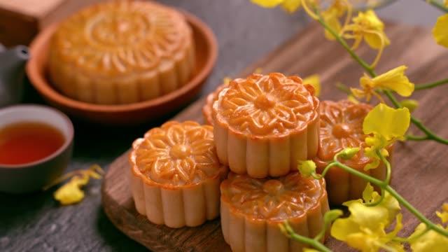 美麗的月餅在木託盤與茶和花在黑色石板背景。中國傳統的中秋節理念。 - chinese new year 個影片檔及 b 捲影像