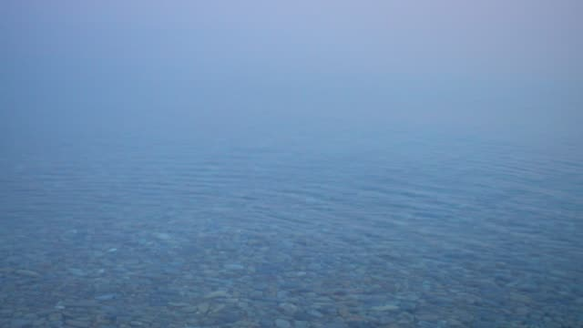 beautiful morning calm water surface with fog. - спокойная вода стоковые видео и кадры b-roll