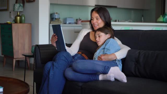stockvideo's en b-roll-footage met mooie moeder en dochter knuffelen op de bank terwijl moeder een verhaal op tablet hardop leest - een tablet gebruiken