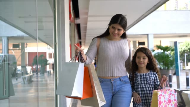 Beautiful mother and daughter walking while looking at the retail displays in the mall