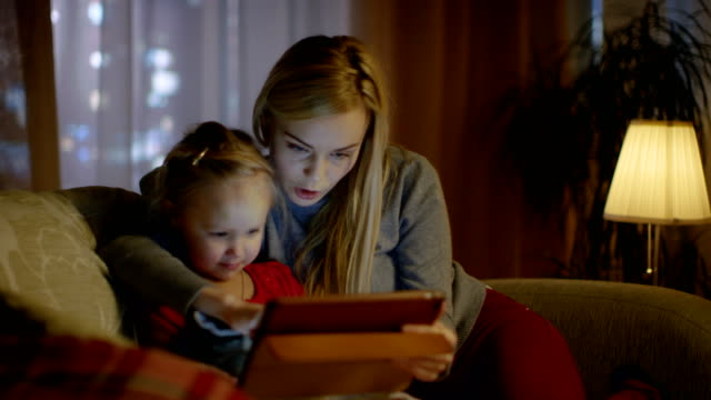 Beautiful Mother and Her Little Daughter are Sitting on a Sofa in the Living Room, They Use Tablet Computer. It's Evening, Room is Cozy and Warm.