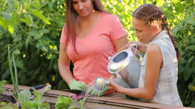 Belle mère jardiner avec sa fille âgée élémentaire - Vidéo
