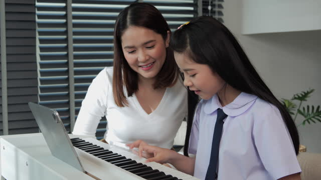 Beautiful mother looking her daughter playing piano at home. She was delighted that her daughter could play the piano.