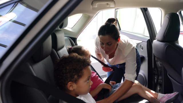 Beautiful mother securing with seat belts her son and daughter at the back of the car seat