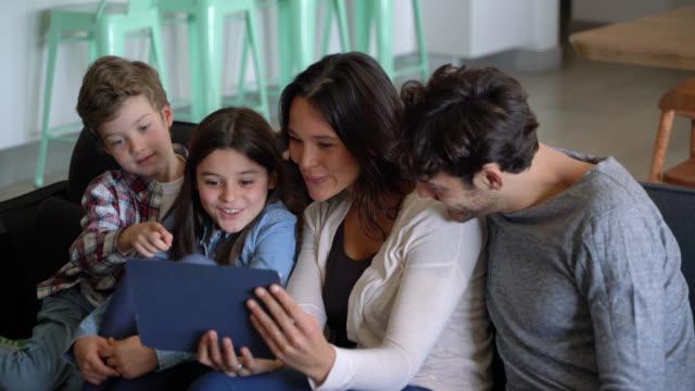 stockvideo's en b-roll-footage met mooie moeder toont iets op tablet aan haar twee kinderen en man terwijl zittend op de bank - vier personen