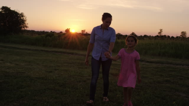 Beautiful mother skipping with her daughter in the grass at sunset video